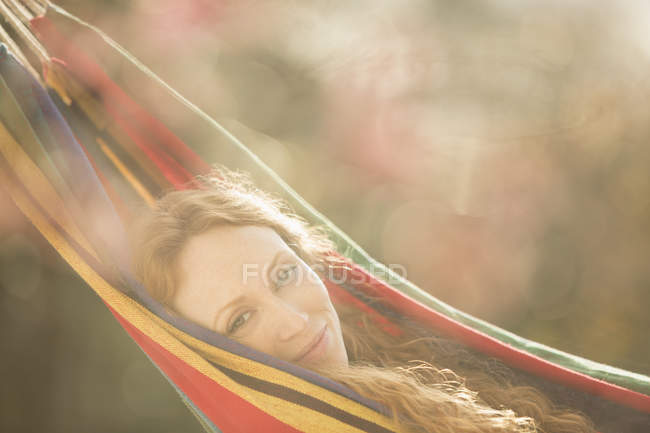 Portrait serene woman relaxing laying in hammock — Stock Photo