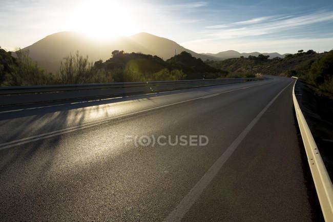 Sonne über Bergen und offener Straße — Stockfoto