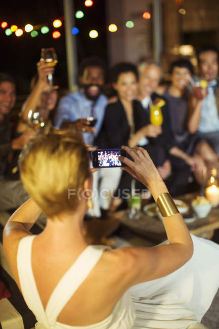 Woman taking picture of friends at party — Stock Photo