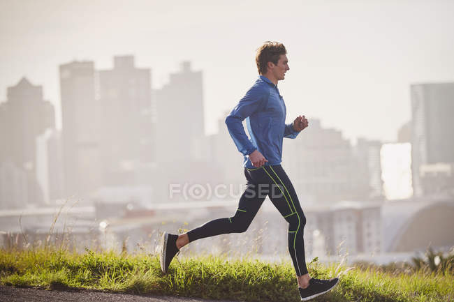 Masculino corredor executando no ensolarado urbano rua — Fotografia de Stock
