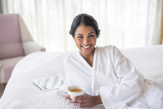 Портрет улыбается женщина в Халат, пить чай на кровати — стоковое фото