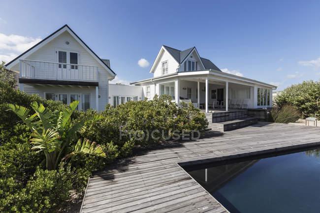 Sunny casa moderna bianca vetrina esterna oltre piscina — Foto stock