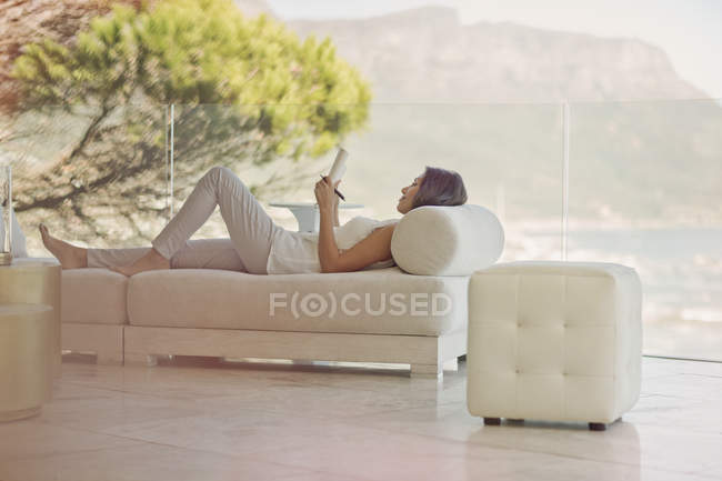 Serene woman doing crossword puzzle on chaise lounge on luxury balcony — Stock Photo