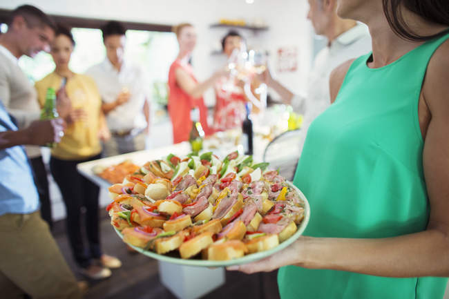 Woman serving tray of food at party — Stock Photo