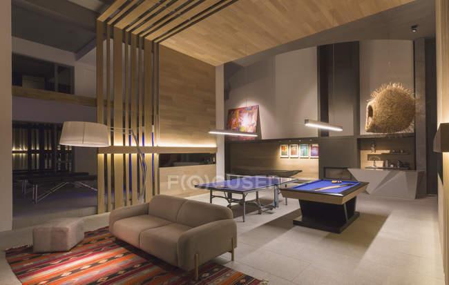 Освещённый бильярдный стол и стол для пинг-понга в современной, роскошной игровой комнате — стоковое фото