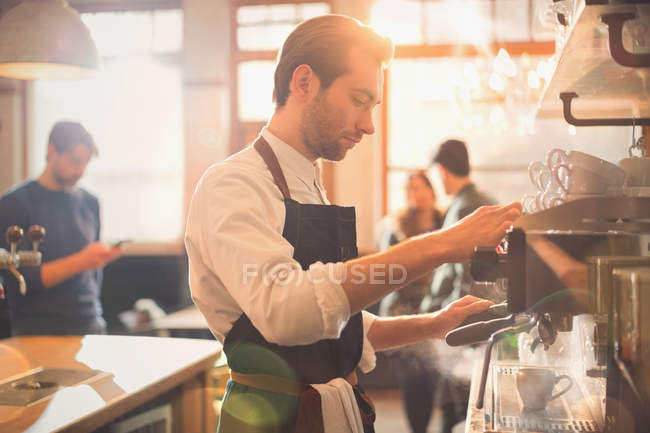 Male barista using espresso machine in cafe — Stock Photo
