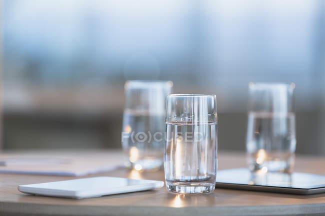 Вода в окулярах поруч із цифрових планшетів на стіл — стокове фото