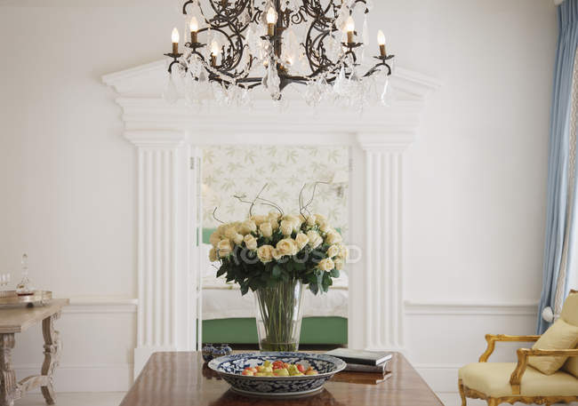 Kronleuchter über Rosenstrauß auf Tisch im Luxusfoyer — Stockfoto