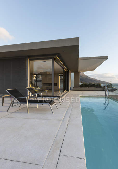 Lounge chairs along lap swimming pool outside modern luxury home showcase exterior — Stock Photo