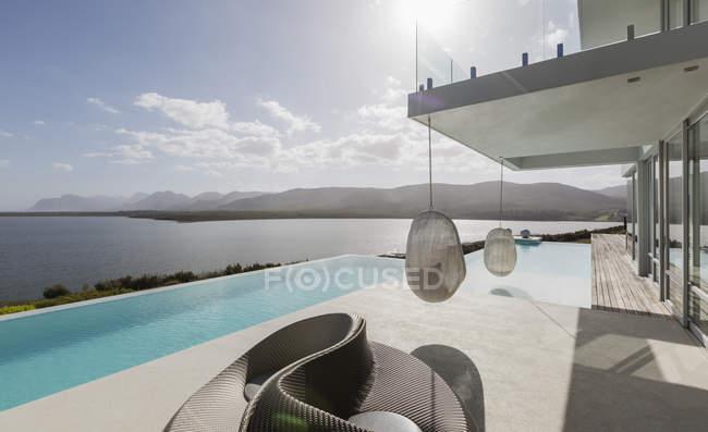 Переглянути Сонячний сучасну розкіш додому Вітрина екстер'єр з пейзажного басейну і океан — стокове фото
