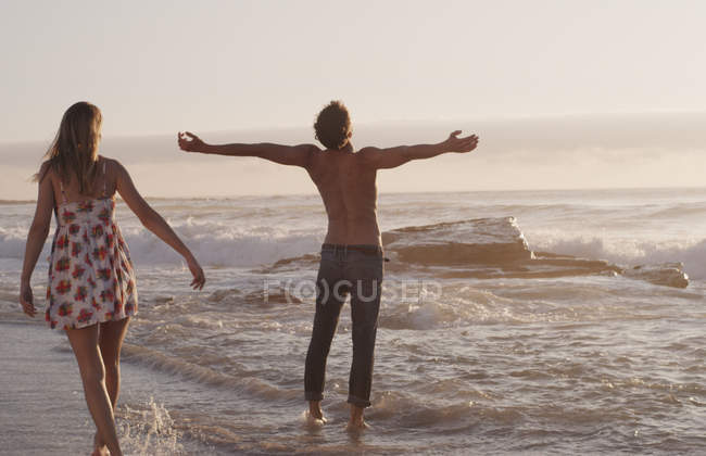 Young woman watching exuberant young man with arms outstretched in ocean surf — Stock Photo