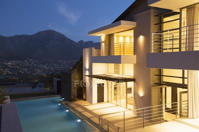 Modern house with swimming pool illuminated at night — Stock Photo
