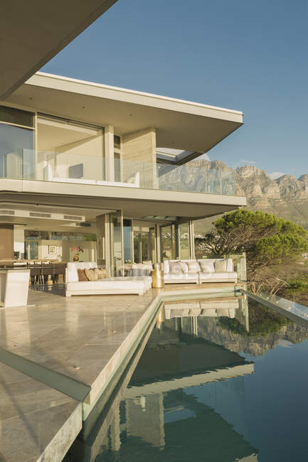 Солнечный современный витринный патио с бассейном и видом на горы — стоковое фото