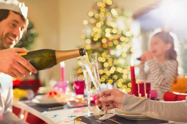 Муж наливает жене шампанское за рождественским столом — стоковое фото