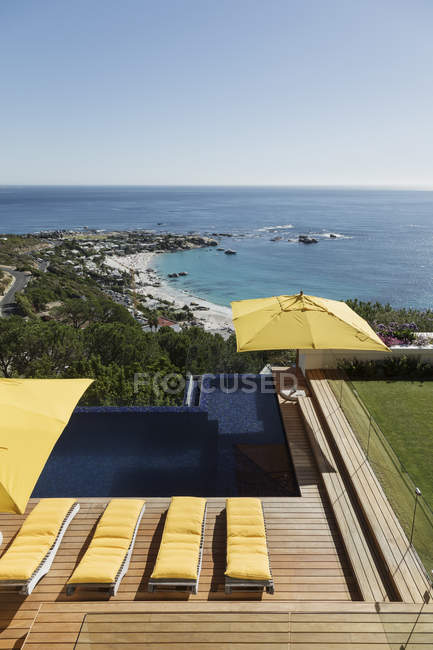 View of ocean beyond luxury swimming pool and patio — Stock Photo