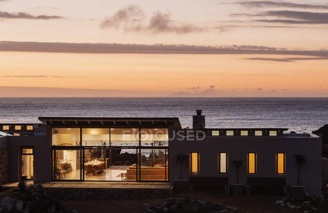 Beleuchtete Luxus Haus mit Blick auf Meer bei Sonnenuntergang — Stockfoto