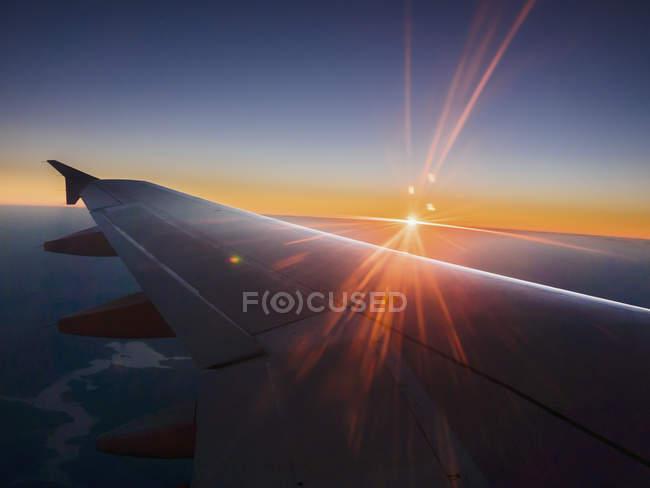Pôr do sol atrás da asa do avião no céu — Fotografia de Stock