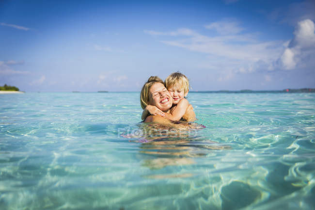 Enthusiastic mother hugging son in tropical ocean — Stock Photo