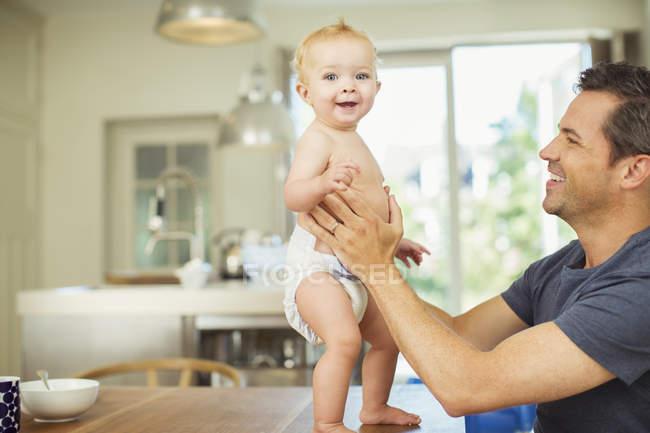 Батько, допомагаючи дитини ходити по таблиці — стокове фото