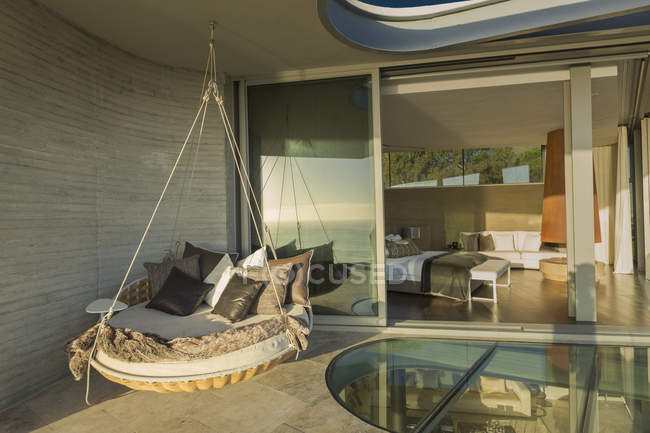 Hanging cushion bed on sunny modern luxury home showcase patio — Stock Photo
