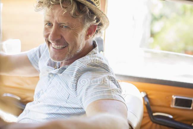 Взрослый мужчина водит машину в солнечный день — стоковое фото