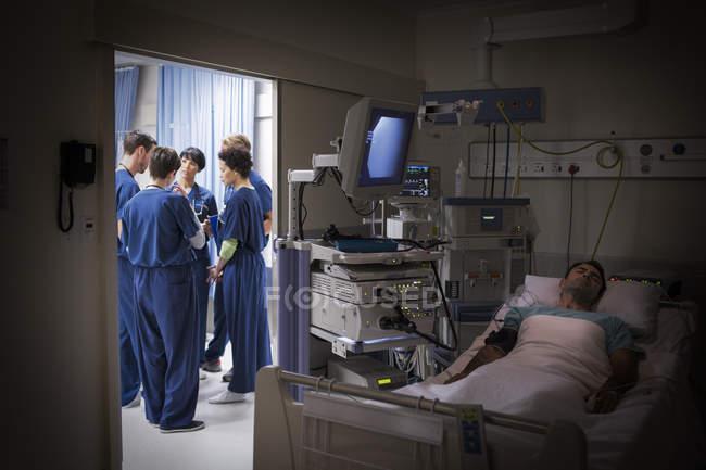 Пациент лежит в постели в отделении интенсивной терапии, команда врачей обсуждают на заднем плане — стоковое фото