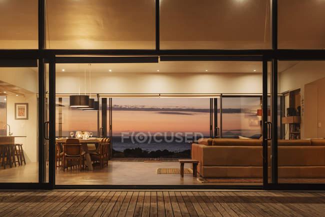 Illuminated home showcase interior overlooking ocean at sunset — Stock Photo