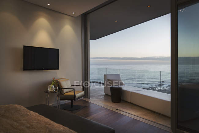 Tranquil twilight ocean view beyond modern luxury home showcase balcony — Stock Photo