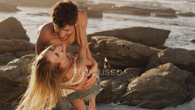 Playful young couple hugging on rocks at ocean — Stock Photo