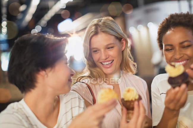 Junge Frauen Essen Muffins zusammen — Stockfoto