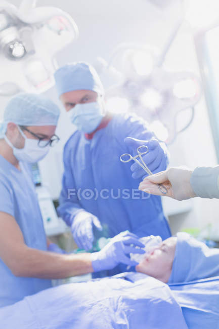 Surgeon reaching for surgical scissors in operating room — Stock Photo