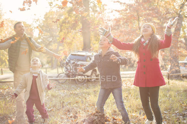 Famiglia che gioca insieme nel parco autunnale — Foto stock