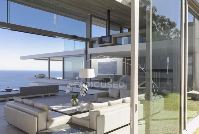 Moderna, casa de luxo vitrine interior sala de estar com vista para o mar — Fotografia de Stock