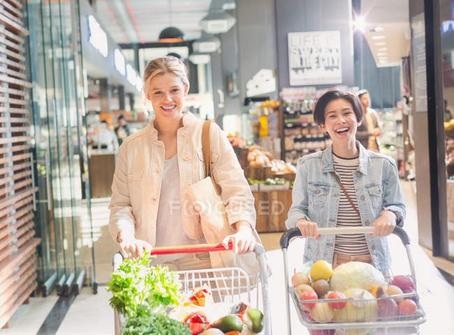 Smiling young women pushing shopping carts in grocery store market — Stock Photo