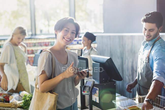Retrato sorridente jovem mulher no supermercado checkout — Fotografia de Stock