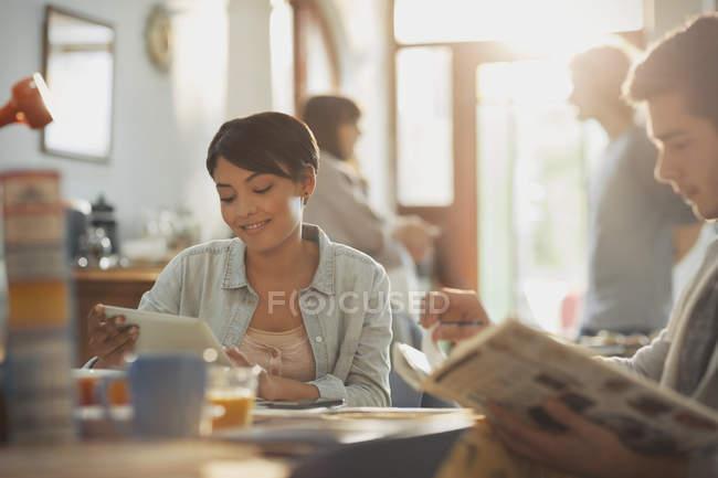 Joven hombre y mujer los estudiantes universitarios estudiando con el libro y tableta digital en mesa - foto de stock
