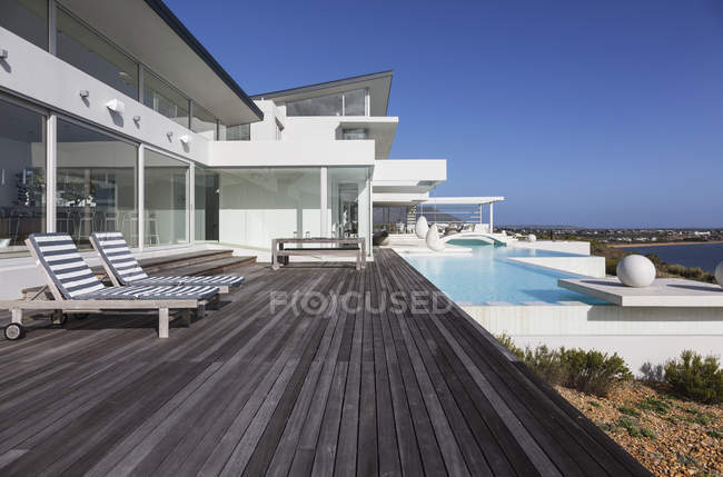 Sonnige moderne Luxus nach Hause Schaufenster außen Terrasse mit Infinity-pool — Stockfoto