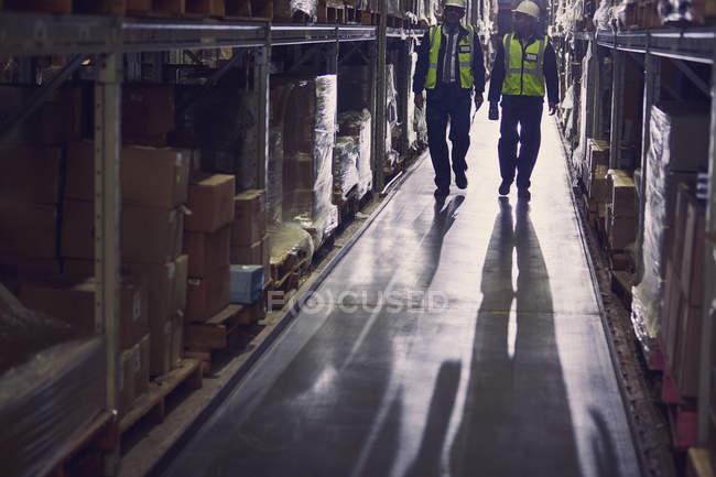 Працівників, гуляючи по товарів і на полицях розподілу складу проходу — стокове фото