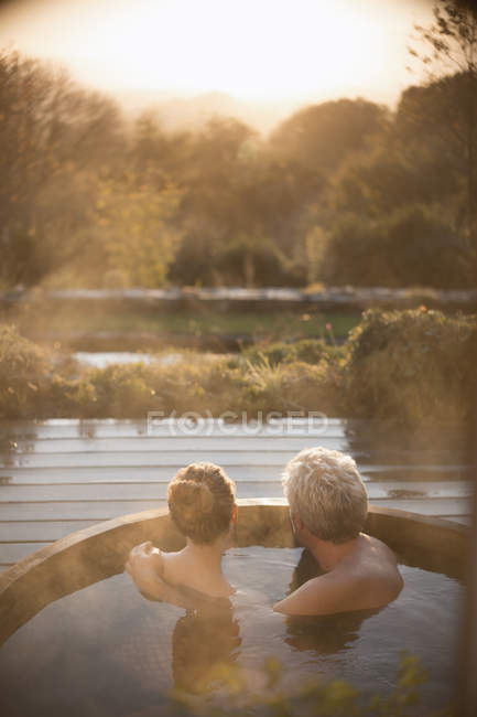 Serene affectionate couple soaking in hot tub on patio with autumn view — Stock Photo