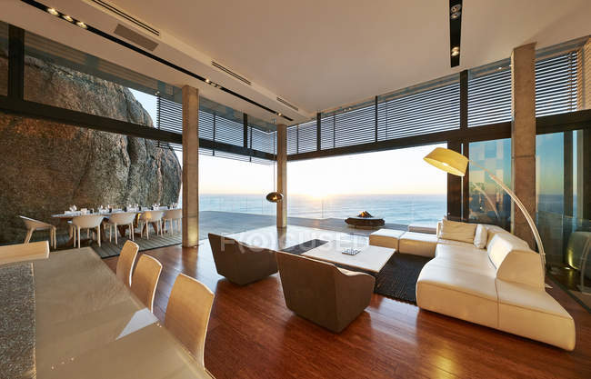 Modern luxury living room open to patio with sunset ocean view — Stock Photo