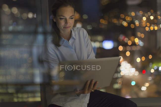 Серйозний бізнес-леді опрацюванні пізно ноутбук в офісі вікно вночі — стокове фото