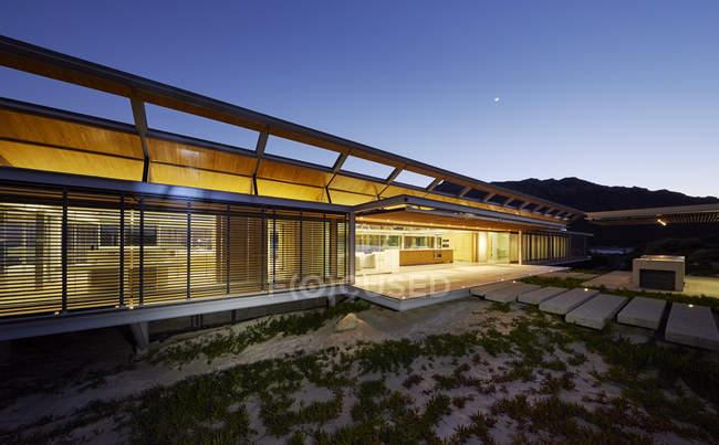 Illuminated modern luxury house at dusk — Stock Photo