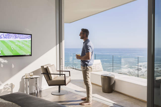 Man watching soccer on TV at sunny luxury patio doorway with ocean view — Stock Photo