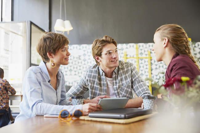 Gli uomini d'affari si incontrano in caffè utilizzando tablet digitale — Foto stock