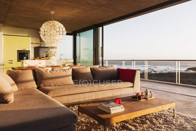Sofa and coffee table in modern living room overlooking ocean — Stock Photo