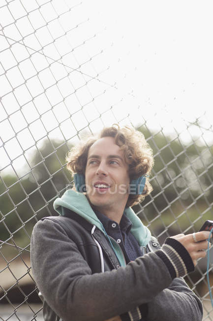 Man listening to headphones against chain link fence — Stock Photo