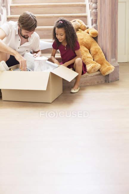 Padre e hija mirando a través de la caja móvil - foto de stock