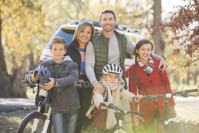 Retrato família sorridente com bicicletas ao ar livre — Fotografia de Stock