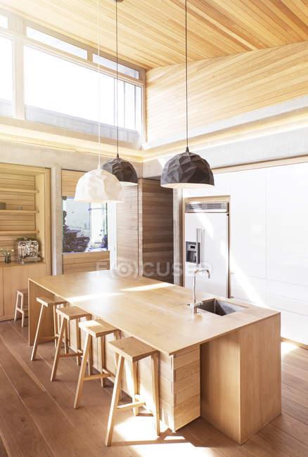 Luzes pingente moderno pendurado sobre ilha de cozinha de madeira — Fotografia de Stock