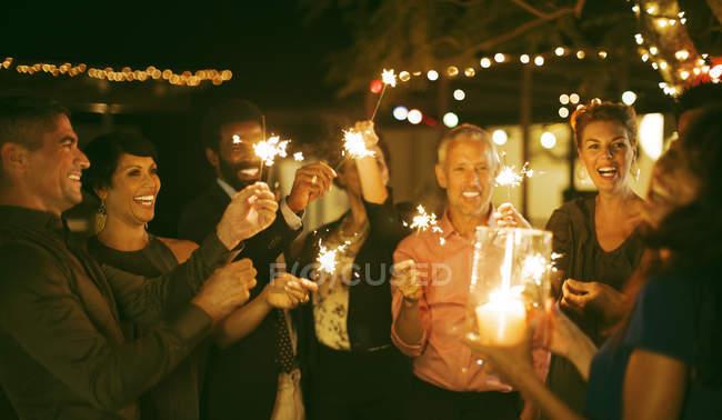 Freunde mit Wunderkerzen auf Party spielen — Stockfoto